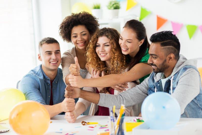 Équipe heureuse à la fête au bureau montrant des pouces  image stock