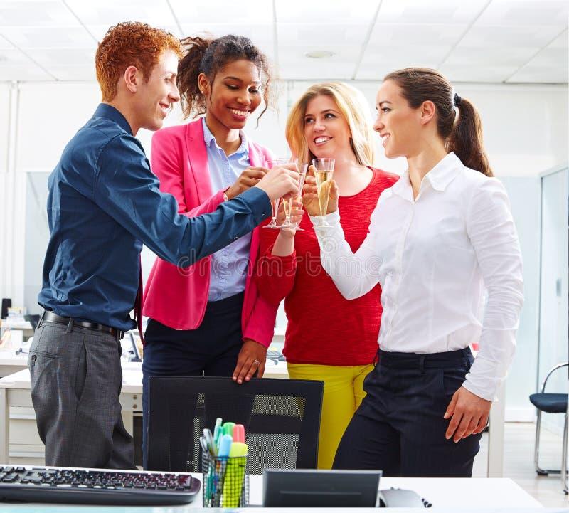 Équipe heureuse d'affaires grillant avec le champagne images stock