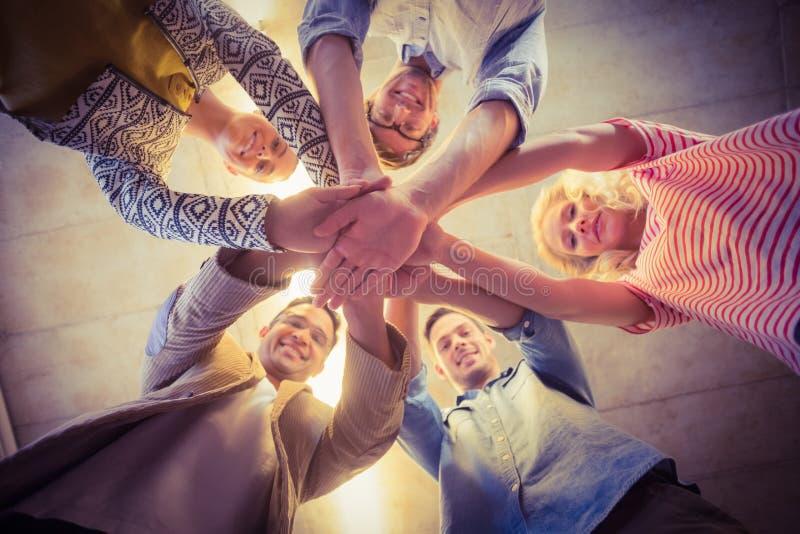 Équipe heureuse d'affaires joignant leurs mains photos stock