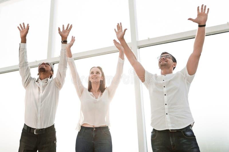 Équipe heureuse d'affaires se tenant ensemble et soulevant leurs mains  photo stock
