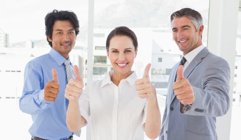 Équipe heureuse de travail renonçant à des pouces images libres de droits