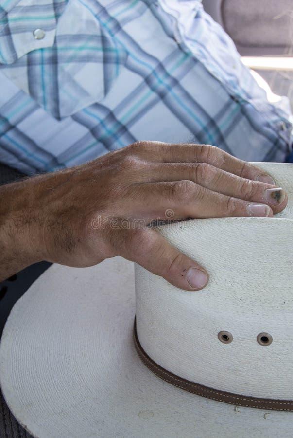 ?quipe la main s'?tendant sur le chapeau de cowboy photos libres de droits