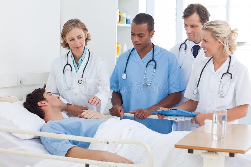Équipe médicale autour du lit d'un patient photographie stock