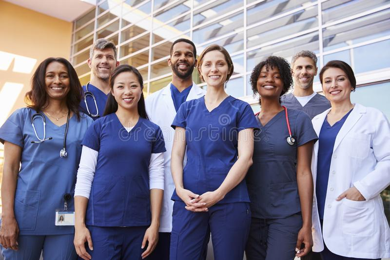Équipe médicale de sourire se tenant ensemble en dehors d'un hôpital image libre de droits