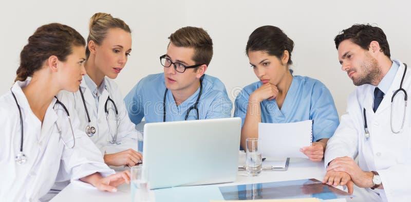 Équipe médicale discutant au-dessus de l'ordinateur portable image libre de droits