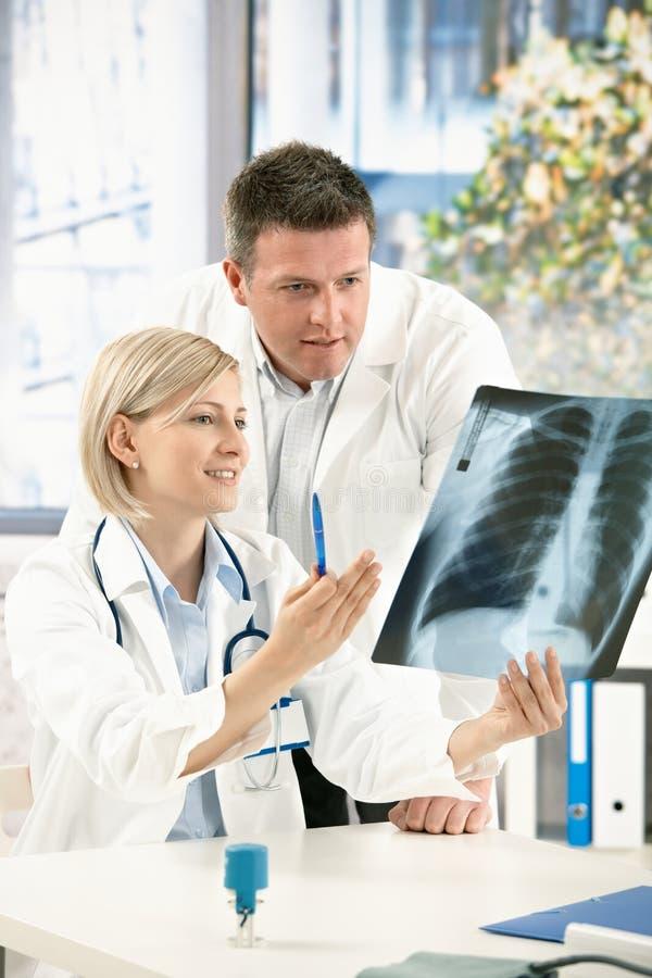 Équipe médicale discutant l'image de rayon X photographie stock libre de droits