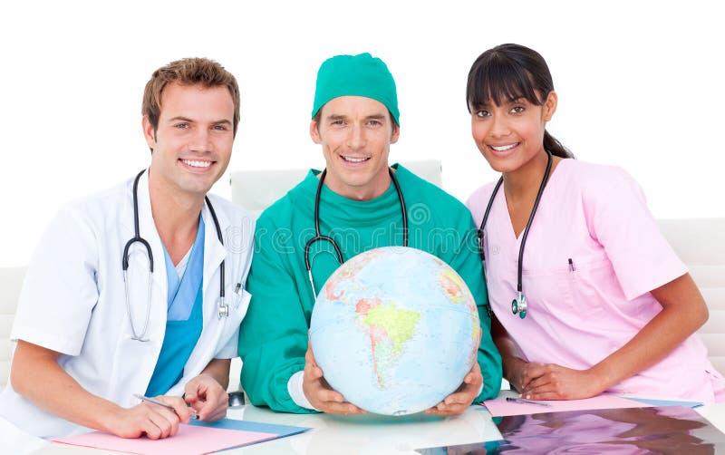 Équipe médicale joyeuse regardant le globe terrestre photos stock