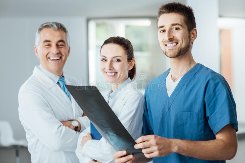 Équipe médicale posant et examinant une image de rayon X photos stock