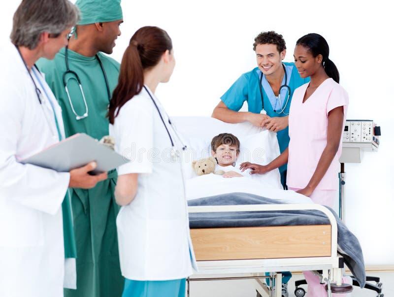 Équipe médicale positive prenant soin d'un petit garçon photos stock