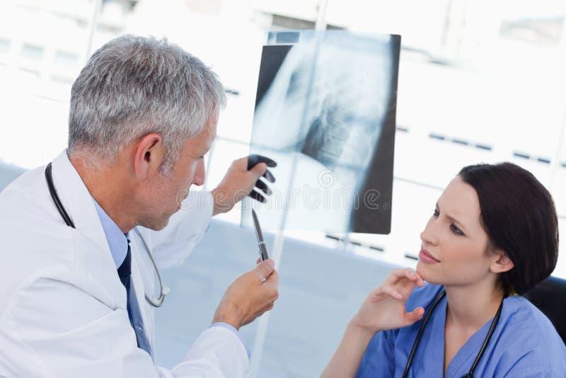 Équipe médicale sérieuse regardant un rayon X photos stock