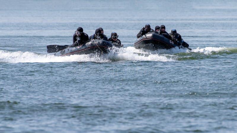 Équipe militaire de force spéciale de marine dans l'action avec des armes à feu et des suites noires de plongeur image stock