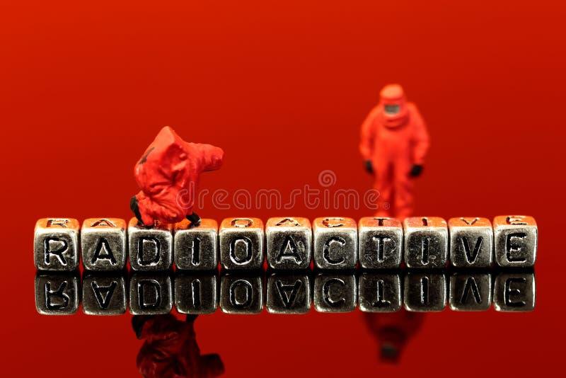 Équipe miniature de modèle d'échelle dans les costumes chimiques avec le mot radioactif images stock