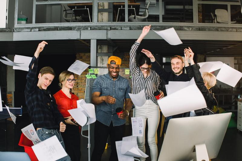 Équipe multi-ethnique d'affaires célébrant pour le succès de travail en rencontrant la finition par des papiers de projet de jet  images libres de droits