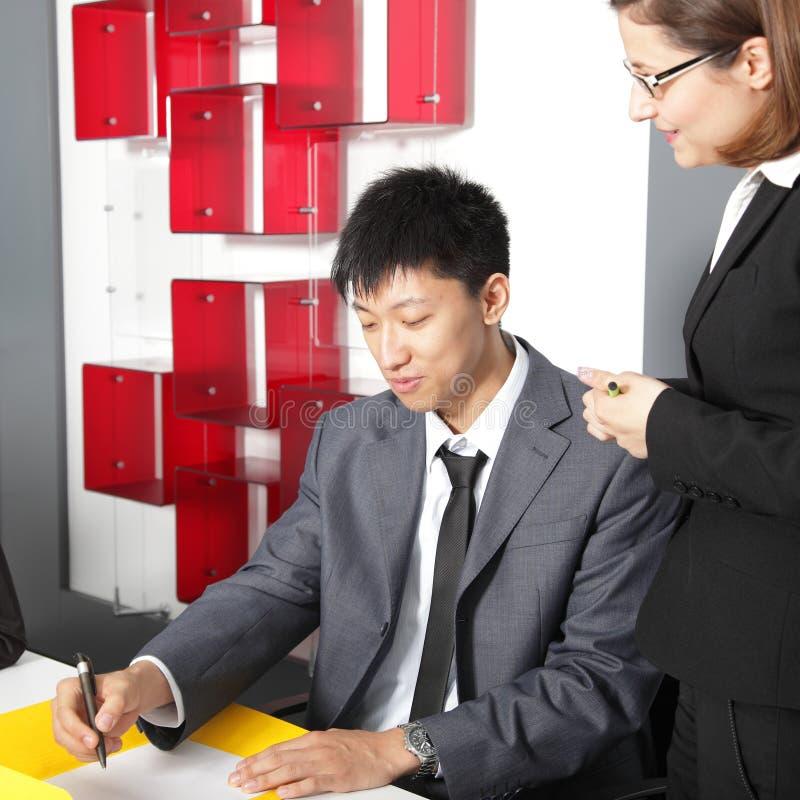Équipe multi-ethnique d'affaires lors d'une réunion assise dans le bureau discutant des écritures images libres de droits