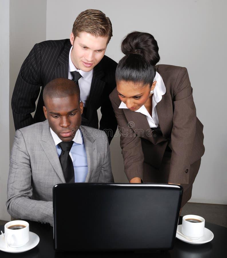 Équipe multi-ethnique d'affaires travaillant sur l'ordinateur portatif images stock
