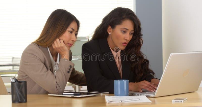Équipe multi-ethnique d'affaires travaillant sur l'ordinateur portatif photographie stock