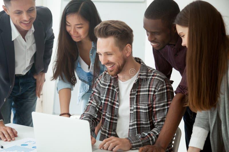 Équipe multi-ethnique heureuse excitée par le résultat en ligne regardant le lapt photos libres de droits