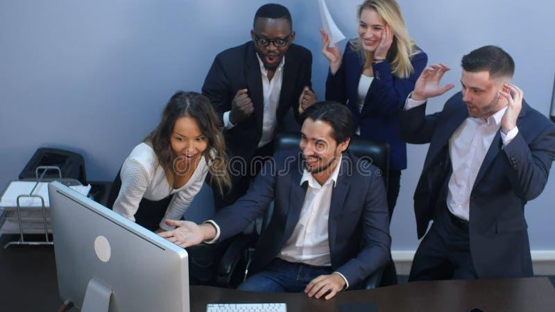 Équipe multiraciale d'affaires célébrant le succès dans le bureau photographie stock libre de droits