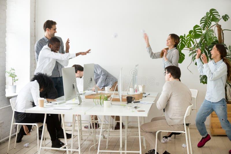 Équipe multiraciale heureuse jetant les boules de papier chiffonnées ayant l'amusement images libres de droits