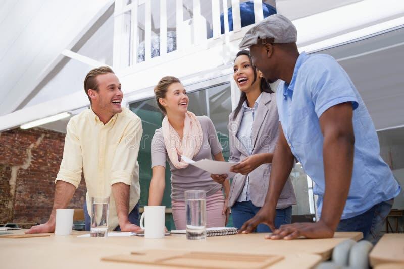 Équipe occasionnelle d'affaires souriant ensemble au bureau image stock