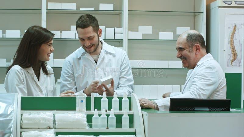 Équipe positive de pharmaciens regardant la boîte du comprimé la pharmacie d'hôpital images stock