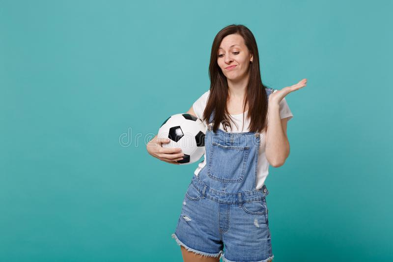 Équipe préférée confuse de jeune femme de soutien déçu de passioné du football avec du ballon de football d'isolement sur la turq photos libres de droits
