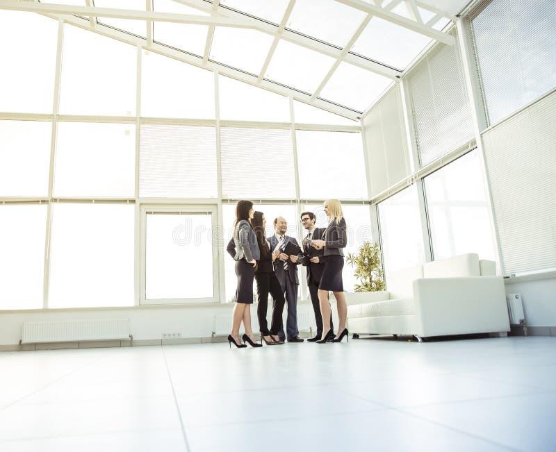 Équipe professionnelle d'affaires se tenant dans le coin le plus éloigné du bureau spacieux images libres de droits