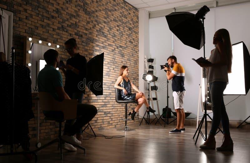 Équipe professionnelle travaillant avec le modèle photographie stock