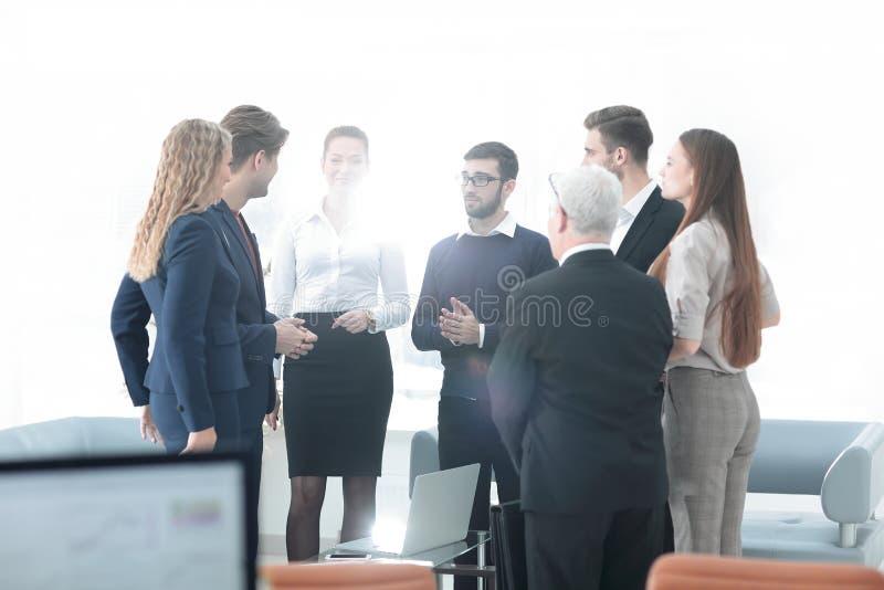 Équipe réussie d'affaires discutant des documents et des idées tenant le bureau proche photo stock