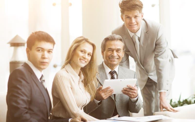 Équipe sérieuse d'affaires avec des tablettes, documents ayant la discussion dans le bureau image libre de droits