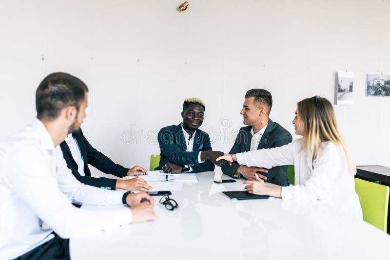 Équipe sûre d'affaires d'âges mélangés et d'appartenance ethnique faisant la poignée de main tandis que réunion dans un bureau mo images libres de droits