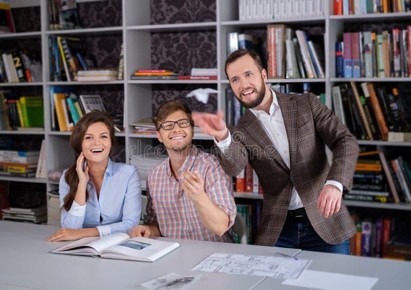Équipe sûre d'ingénieurs ayant l'amusement dans un studio d'architecte images stock