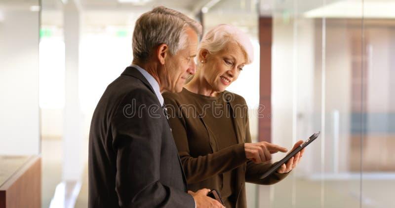 Équipe supérieure d'affaires allant au-dessus des données financières sur le comprimé dans le couloir photo stock