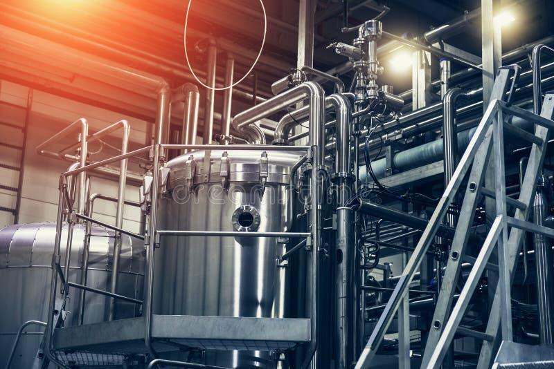 Équipement de brassage d'acier inoxydable : grands réservoirs ou réservoirs et tuyaux dans l'usine moderne de bière image stock