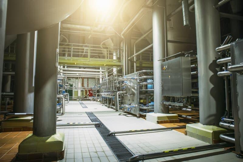 Équipement de brassage d'acier inoxydable : grands réservoirs ou réservoirs et tuyaux dans l'usine moderne de bière Production de image libre de droits