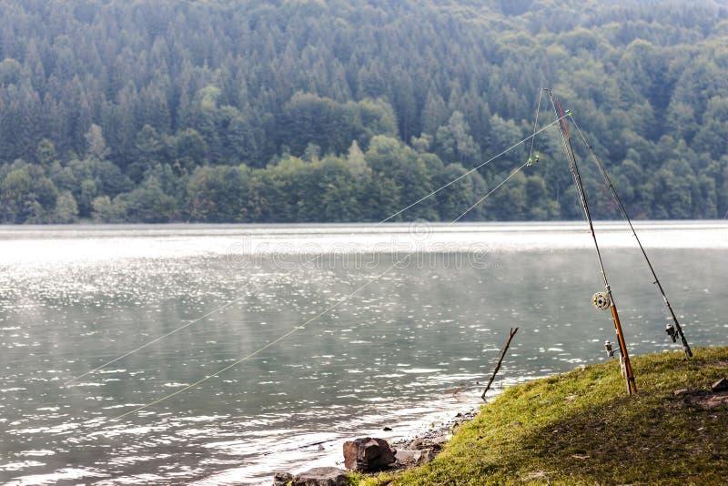 Équipement de canne à pêche sur un lac dans le matin brumeux de ressort photos libres de droits