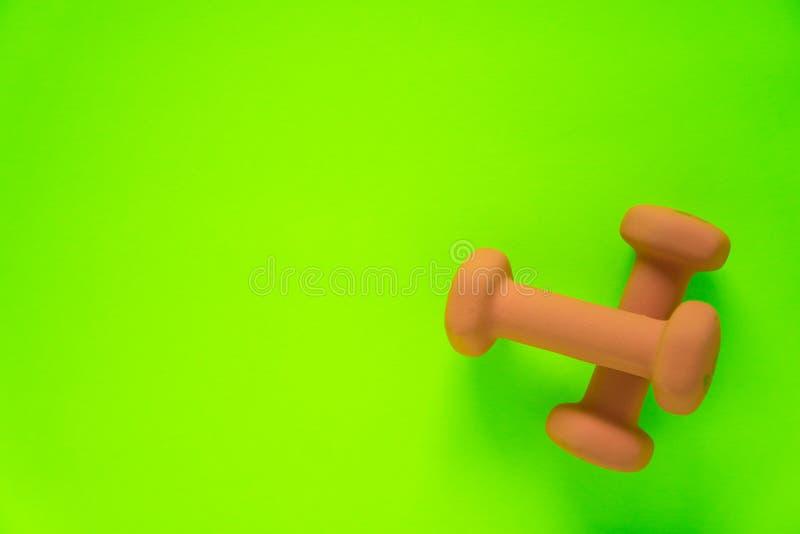 Équipement de forme physique avec les haltères jaune-orange des poids des femmes d'isolement sur un vert de chaux avec le fond de photos stock
