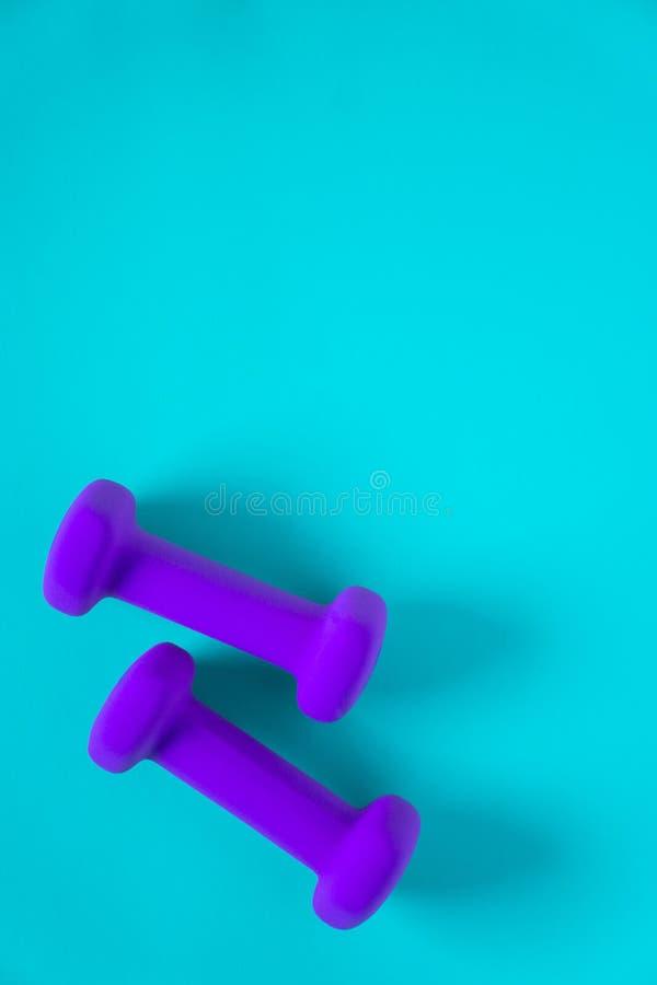 Équipement de forme physique avec les haltères pourpres des poids des femmes d'isolement sur un fond clair de bleu de ciel avec l images stock