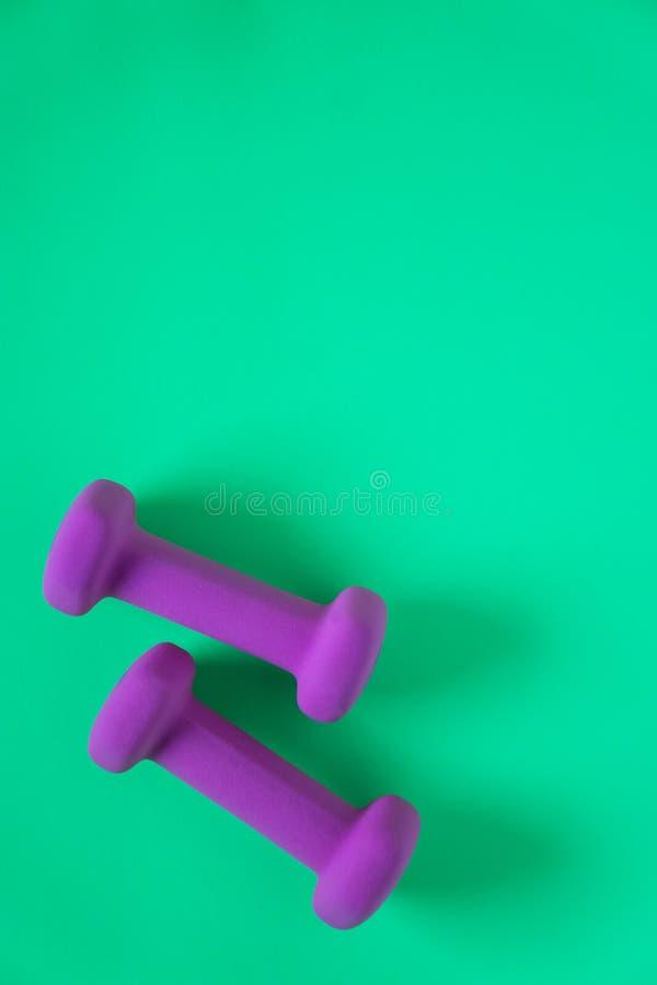 Équipement de forme physique avec les haltères pourpres des poids des femmes d'isolement sur un fond de vert de sarcelle d'hiver  image stock
