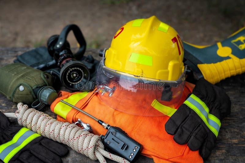 Équipement de sapeur-pompier placé sur le fond en bois de table images libres de droits