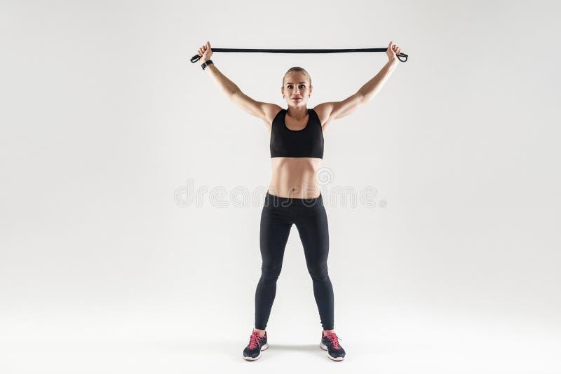 Équipement de Trx Femme forte tenant la corde à sauter près de la tête image stock