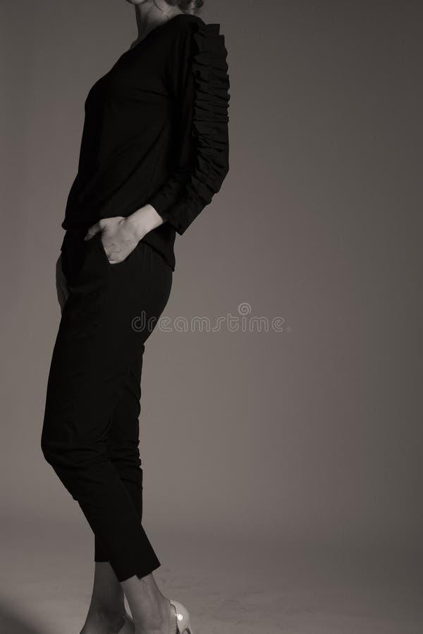 Équipement noir élégant pour des femmes dans le studio, coiffuree moderne photographie stock libre de droits