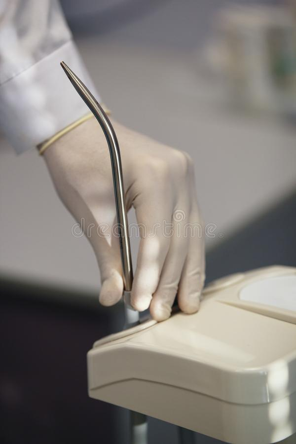 Équipement professionnel de stomatologie d'utilisation de dentiste dans la chambre de chirurgie - salivator image stock