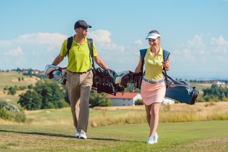Équipements de port de golf de couples heureux et sacs de transport de support images stock