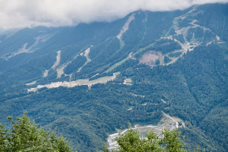 Équipements de sports et bâtiments résidentiels sur la pente d'une haute montagne avec une pente verte et le dessus dans les nuag photos libres de droits