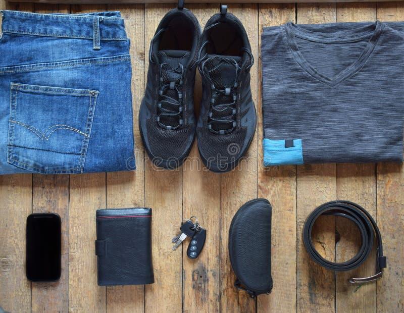 Équipements occasionnels d'hommes Chaussures, habillement et accessoires d'hommes sur le fond en bois - T-shirt gris, blues-jean, photographie stock