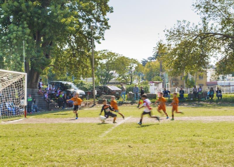 Équipes d'enfants jouant le football Sunny Day en Uruguay photographie stock