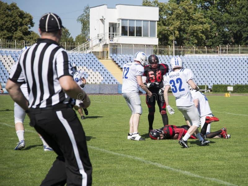 Équipes pour le football américain contre le contexte d'un champ vert photos stock