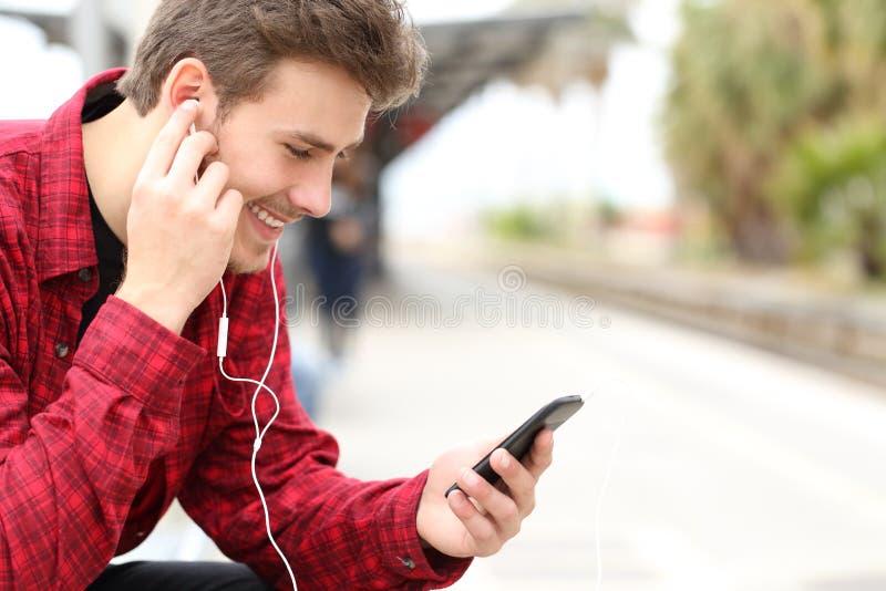 Équipez écouter la musique attendant dans une station de train photos libres de droits