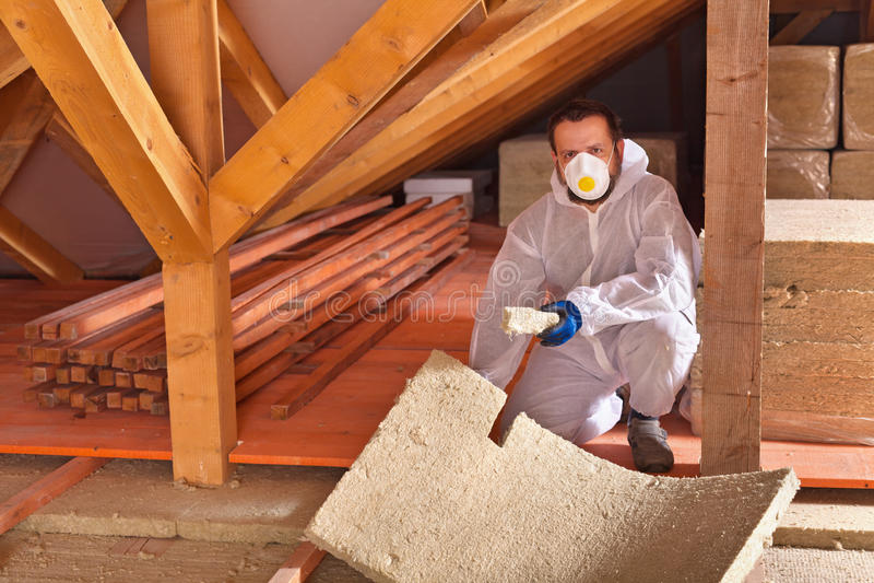 Équipez étendre des panneaux d'isolation thermique dans une nouvelle maison photographie stock libre de droits